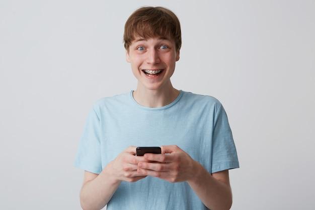 Closeup de jovem animado e alegre com aparelho nos dentes, usa camiseta azul e se sente feliz usando o smartphone isolado sobre a parede branca