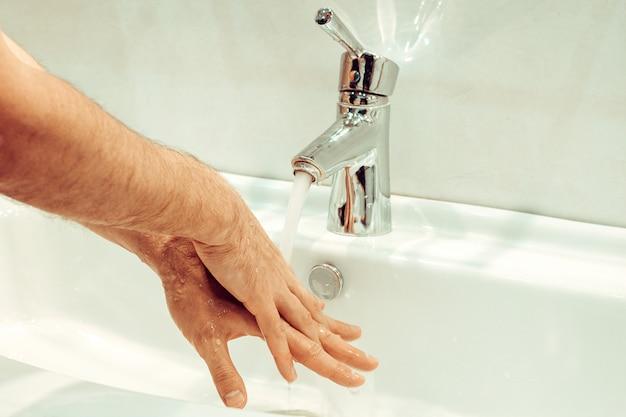 Closeup de jovem homem caucasiano lavando as mãos com sabão na pia do banheiro higiene pessoal