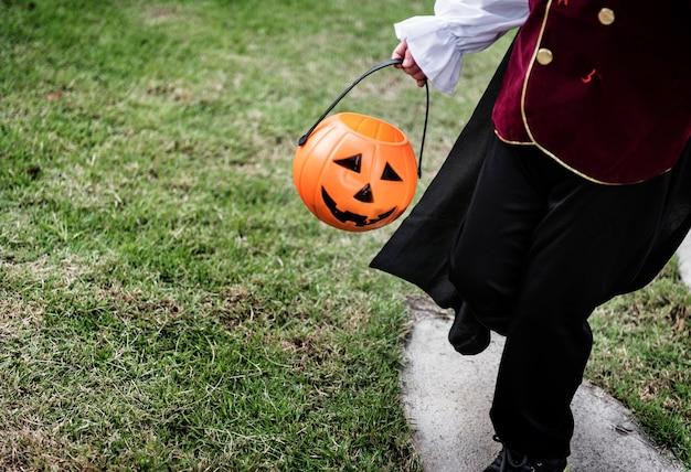Closeup de jovem pirata segurando balde de halloween