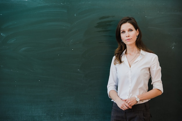 Closeup de jovem professora contra lousa em classe