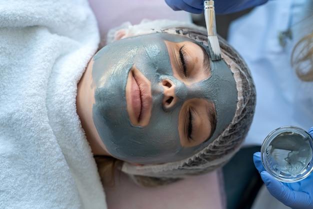 Closeup de jovem recebendo massagem spa facial procedimento hidratante por dermatologista na clínica de beleza. conceito de cuidados com a pele