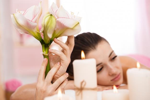 Closeup de jovem relaxante após massagem nas costas, admirando a atmosfera