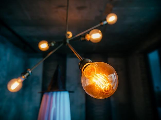Closeup de lâmpada com lâmpadas na parede azul escuro