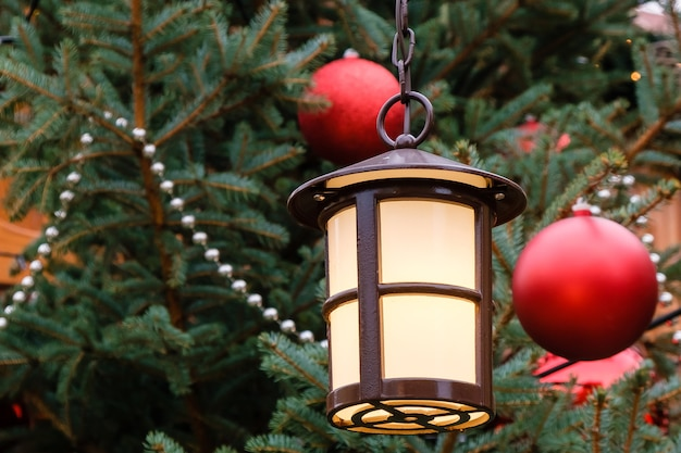 Closeup de lanterna de rua e bolas de natal vermelhas com guirlanda de led na árvore natural decorada de ano novo