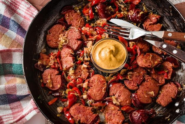 Closeup de linguiça fatiada e mix de vegetais frescos fritos na frigideira rústica com mostarda