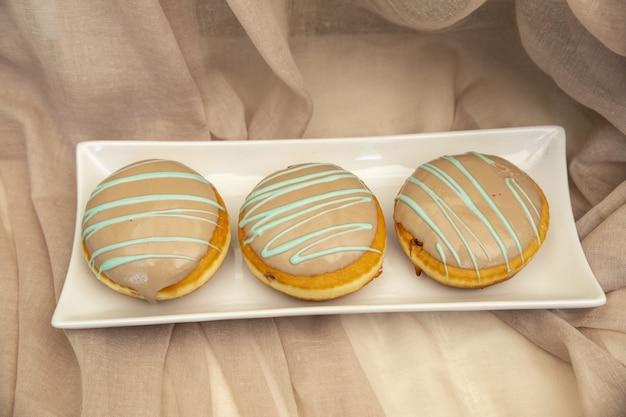 Closeup de macarons com cobertura de caramelo em um prato sob as luzes