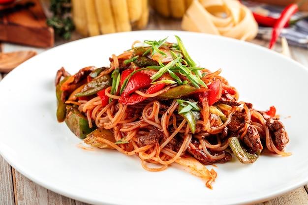Closeup de macarrão asiático com carne e vegetais em prato branco