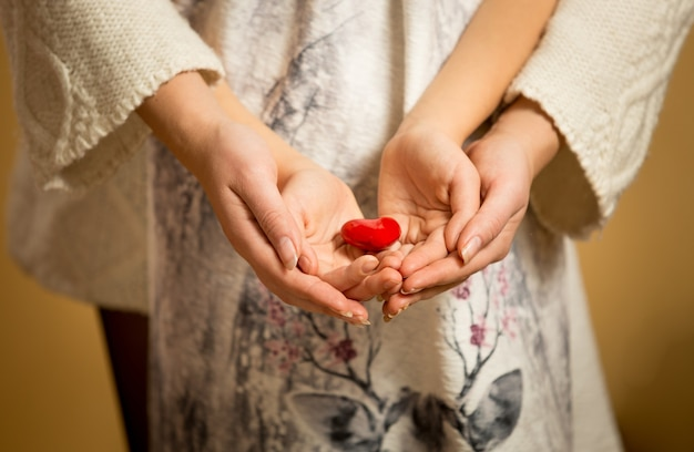 Closeup de mãe e filha segurando um coração vermelho nas mãos