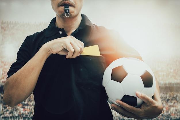 Closeup de mão de árbitro de futebol segurando cartão amarelo isolado no branco com traçado de recorte