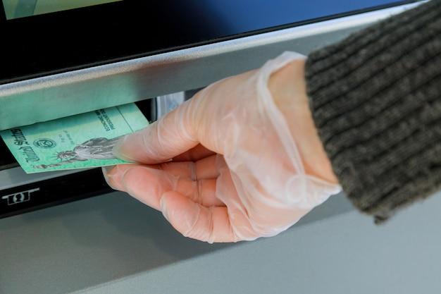 Closeup de mão entrando cheque de estímulo de depósito para transferência de máquina atm