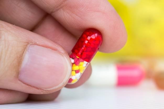 Closeup, de, mão feminina, segurando, colorido, cápsula