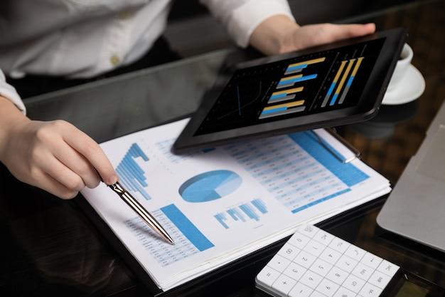 Closeup de mão segurando o tablet e caneta no gráfico