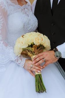 Closeup de mãos casal nupcial com anéis de casamento no fundo da natureza