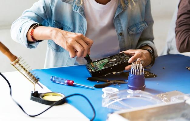 Closeup de mãos com chave de fenda com disco rígido de computador