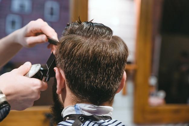 Closeup de mãos de barbeiro cortando cabelo curto para homem usando aparador na barbearia