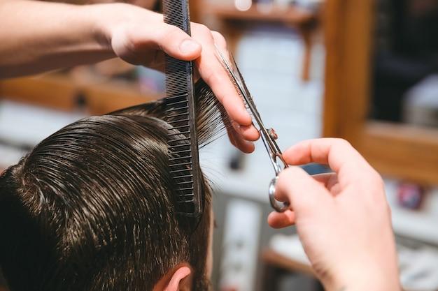 Closeup de mãos de barbeiros fazendo corte de cabelo curto para homem usando pente e tesoura na barbearia