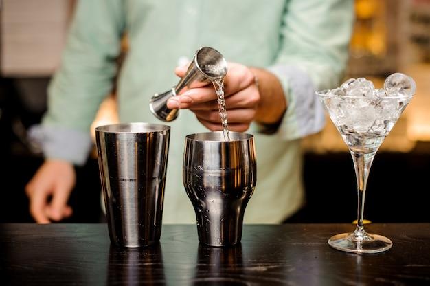 Closeup de mãos de barman derramando bebida em uma coqueteleira para preparar um cocktail
