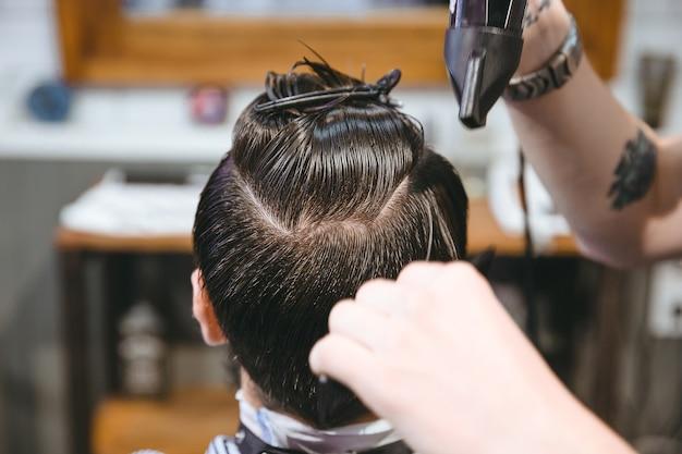 Closeup de mãos de cabeleireiro secando o cabelo de um cliente do sexo masculino usando secador de cabelo e pente na barbearia