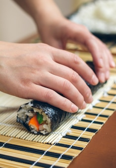 Closeup de mãos de chef mulher enrolando sushi japonês com arroz, abacate e palitos de caranguejo na folha de algas nori