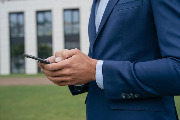 Closeup de mãos de empresário usando compras on-line de comunicação por telefone celular