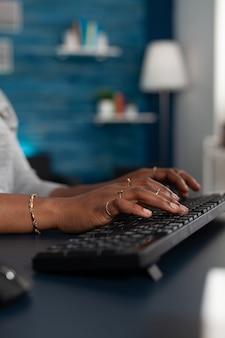 Closeup de mãos de estudante negro digitando no teclado, navegando nas informações on-line na internet