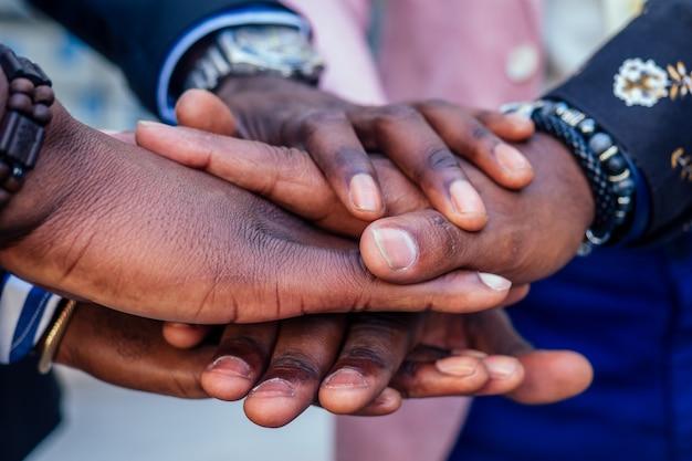 Closeup de mãos de homens de negócios de homens de amigos afro-americanos negros em um elegante terno, relógio de pulso caro, trabalho em equipe, aperto de mão. conceito de negócio bem sucedido e bom negócio