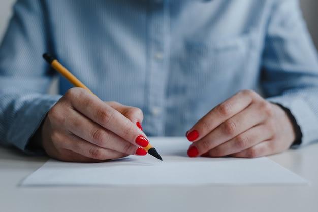 Closeup de mãos de mulher com unhas vermelhas assinando e corrigindo documentos na mesa