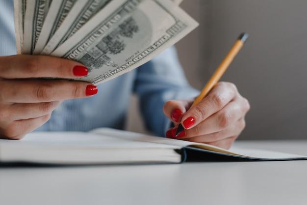Closeup de mãos de mulher com unhas vermelhas segurando notas de dinheiro de cem dólares e fazendo anotações com um lápis
