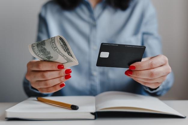 Closeup de mãos de mulher com unhas vermelhas segurando notas de dinheiro de cem dólares e um cartão de crédito preto Foto Premium