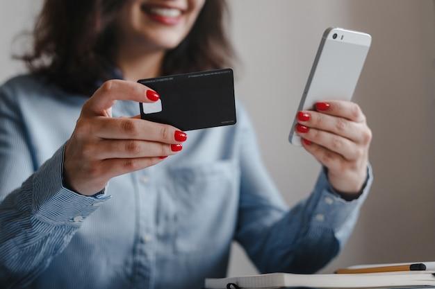 Closeup de mãos de mulher com unhas vermelhas segurando um cartão de crédito e um celular, fazendo o pagamento online