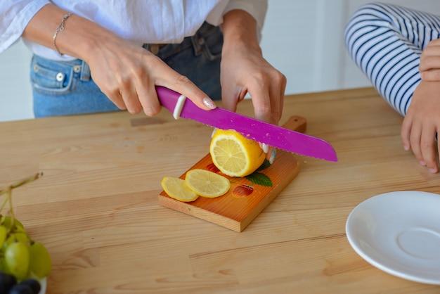 Closeup de mãos de mulher cortando limão com uma faca afiada na cozinha