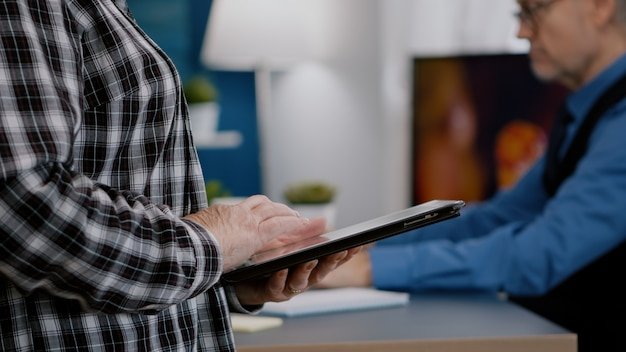 Closeup de mãos de mulher segurando um computador tablet, analisando gráficos em pé no local de trabalho de casa enquanto ...