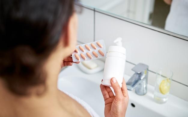 Closeup de mãos de mulher segurando uma garrafa com comprimidos médicos por um lado e blister com pílulas laranja por outro.