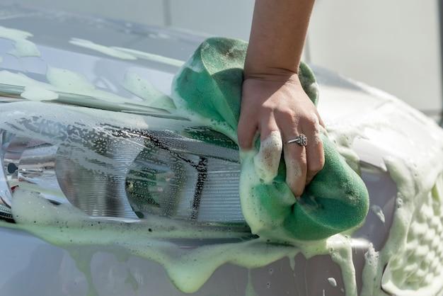 Closeup de mãos de mulher usando esponja verde com espuma de sabão, lavando seu carro moderno