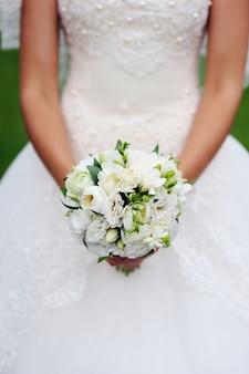 Closeup de mãos de noiva segurando um buquê de casamento bonito