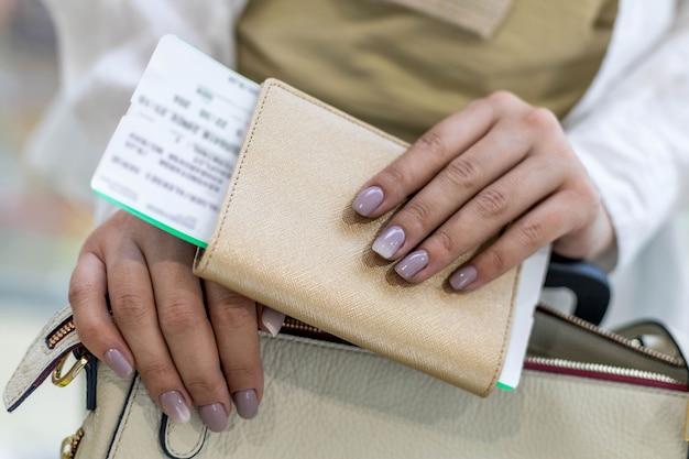 Closeup de mãos de turista verificando documentos, passaporte e passagem, preparando-se para embarque no aeroporto