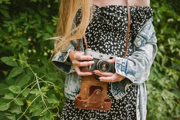 Closeup de mãos de uma mulher segurando uma câmera de filme vintage
