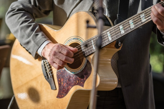 Closeup de mãos do homem tocando violão