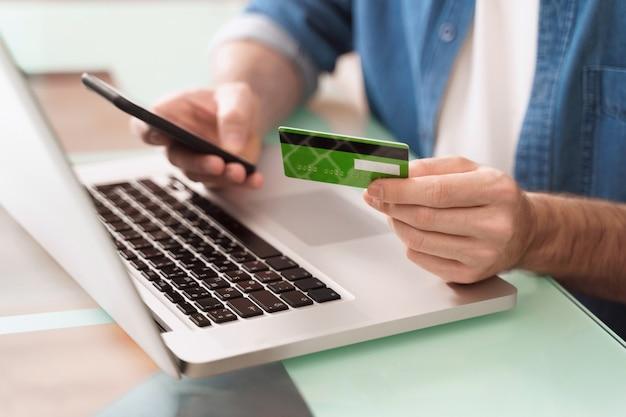 Closeup de mãos do homem usando smartphone, laptop e cartão de crédito para comércio eletrônico.