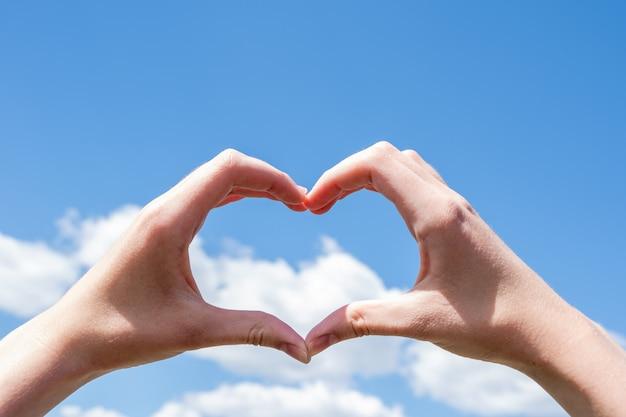 Closeup de mãos fazendo um símbolo de coração