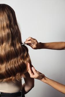 Closeup de mãos femininas de cabeleireiro ou cabeleireiro faz penteado. cabelo