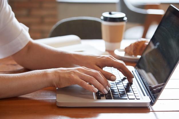 Closeup de mãos femininas, digitando no laptop com copo para viagem e croissant