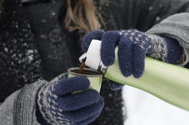 Closeup de mãos femininas em luvas de malha, derramando café quente de uma garrafa térmica em um dia frio de neve do inverno