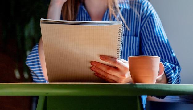 Closeup de mãos femininas segurando o programa de leitura de caderno em um café com uma xícara de café na mesa
