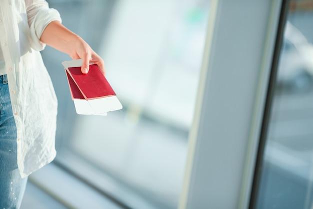 Closeup de mãos femininas segurando passaportes e cartão de embarque no aeroporto