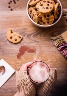 Closeup de mãos femininas segurando um copo de bebida quente sobre uma mesa com biscoitos de chocolate na tigela de estrelas