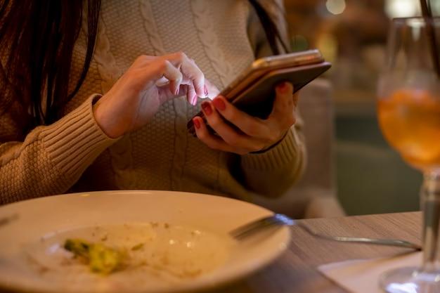 Closeup de mãos femininas segurando um telefone e digitando à noite em um café