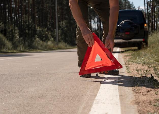Closeup de mãos masculinas colocando a placa de advertência de triângulo vermelho na beira da estrada perto de um carro quebrado no verão