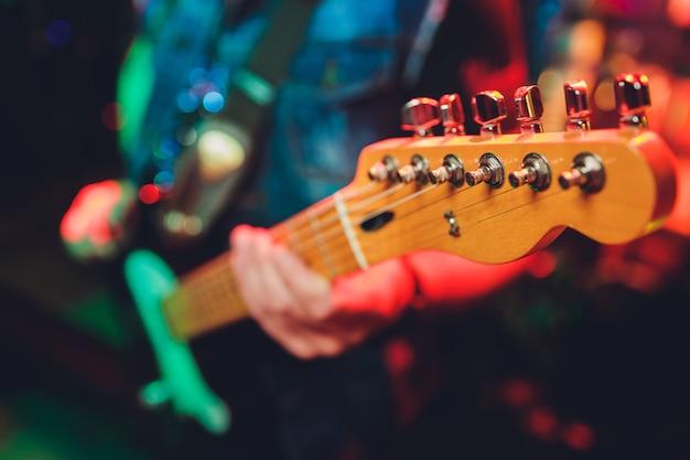 Closeup de mãos masculinas desfocadas, tocando guitarra.