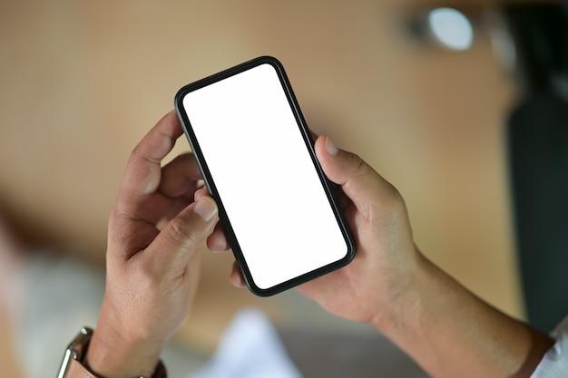 Closeup de mãos masculinas segurando o telefone inteligente móvel de tela em branco